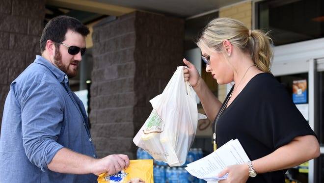 Volunteers Brett Cutrer and Kayla Purvis pick up donations for the United Way of Southeast Mississippi's CANpaign Kickoff event at Corner Market.
