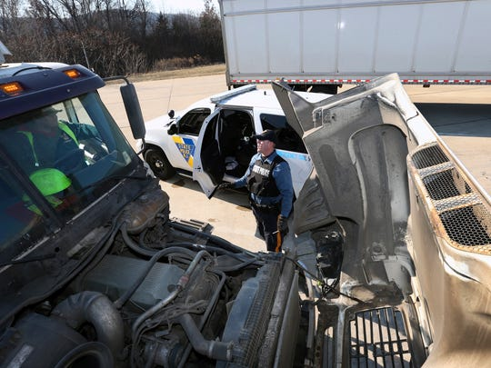 In this Monday, Feb. 6, 2017, photo, New Jersey State Police trooper Jason Salmeri talks with a driver in a truck flagged for further inspection at the Greenwich truck weigh station on Interstate 78, in Greenwich Township, N.J. One of the first lines of defense against New Jersey's opioid epidemic is the highway truck weigh station. (AP Photo/Mel Evans)