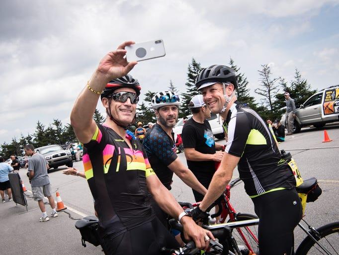 Veteran road cyclist George Hincapie takes a cell phone