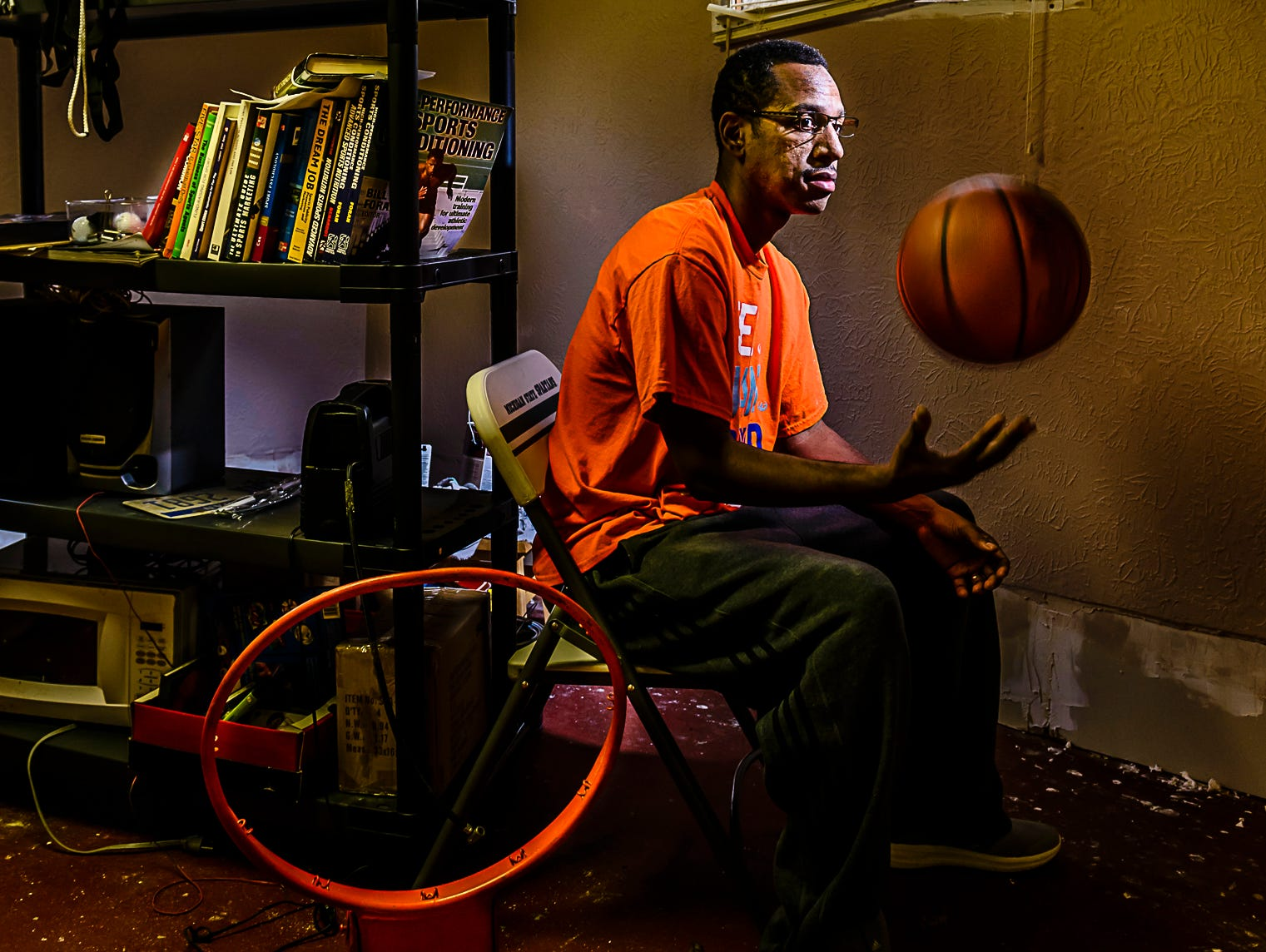 Former Waverly Girl's Basketball Head Coach ,T.J. Hawkins, sits in a stoarge room where he has moved all his athletic paraphenalia at his home in Lansing Thursday January 19, 2017. Hawkins suffered a stroke that forced him to leave his Waverly coaching position and is struggling to recover and regain a coaching position. KEVIN W. FOWLER PHOTO
