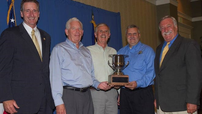 Lt. Gov. Robert Duffy, left, and Jim Trezise, right, present the Governor's Cup trophy to Chateau LaFayette Reneau's Scott Welliver, second from left, Gene Pierce, center, and winemaker Tim Miller during the 2014 New York Wine & Food Classic Aug. 13 at the Watkins Glen Harbor Hotel in Watkins Glen. Trezise is New York Wine and Grape Foundation president, and Welliver and Pierce own the winery.