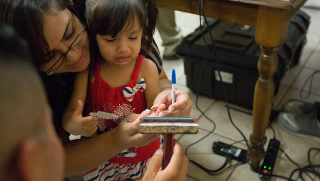 Stephanie Garcia holds her daughter Lynae Olvera,1, while school resource officer Adam Medina helps ink the toddler's fingers during an Ident-A-Chiid program sponsored by the Las Cruces Police Department and held at The Children's Garden on E. Court Ave, Monday, July 3, 2017,