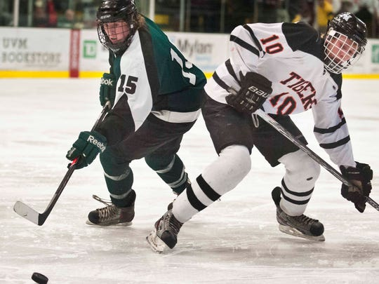 Stowe's Chad Haggerty (left) and Middlebury's Justin Stone eye the puck in the Lake Division state hockey championship in Burlington on Thursday, March 6, 2014.