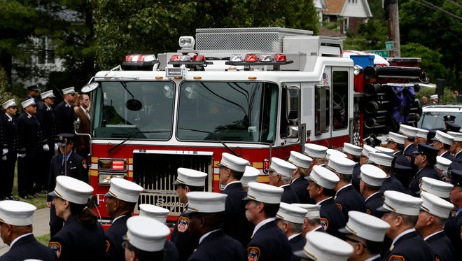 Firefighters line the street Thursday as the body of Lt. Gordon Ambelas is brought to the church for his funeral in the New York City borough of Staten Island. Ambelas got trapped while looking for victims in a high-rise blaze, the first FDNY firefighter to die in the line of duty in more than two years.