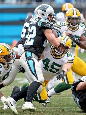 Green Bay Packers nose tackle Kenny Clark (97) and outside linebacker Vince Biegel (45) stop Carolina Panthers running back Christian McCaffrey (22)  on Sunday, December 17, 2017 at Bank of America Stadium in Charlotte, N.C.