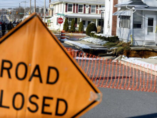 Emergency workers, in the distance at left, stand near a closed-off section of South Grant Street in Palmyra on Wednesday, where a sinkhole has opened up. The newest hole lies very near the site where three depressions developed in October in the 300 block of East Cherry Street, forcing the evacuation of four duplexes and several families. (Jeremy Long   Lebanon Daily News)