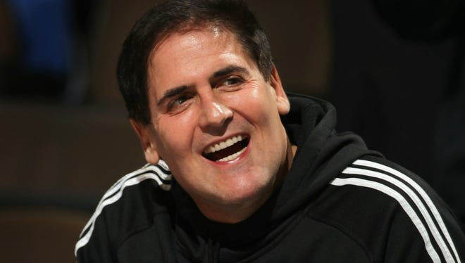 Mark Cuban, owner of the Dallas Mavericks, sits on the bench during warm ups against the Denver Nuggets in 2011.