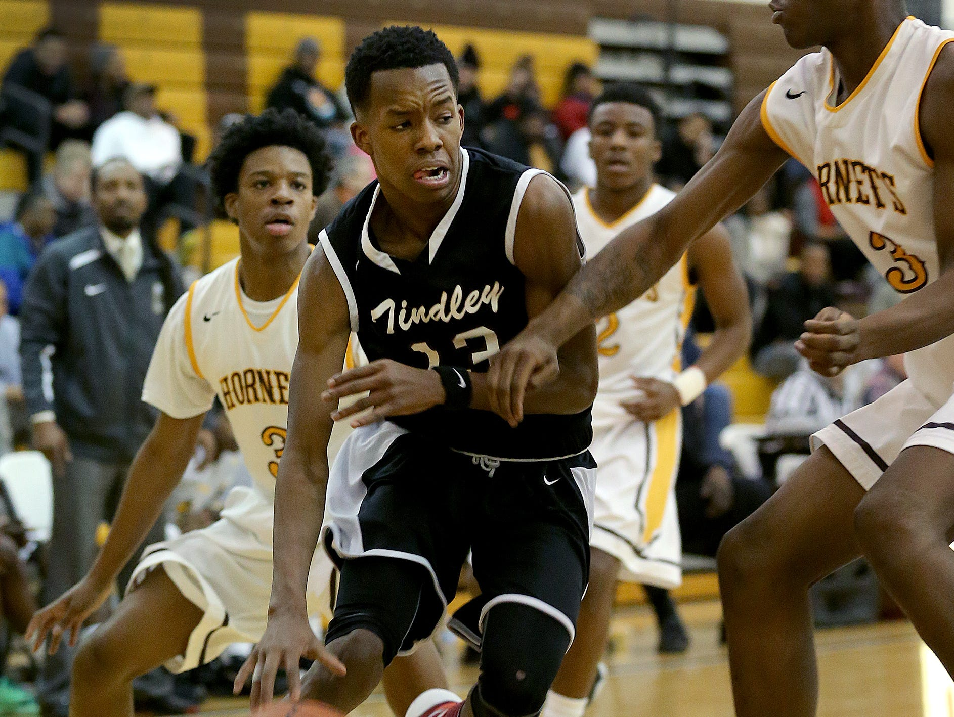 Tindley Tigers Eric Hunter (13) drives by Howe Hornets David Burns (43) and Jermaine Couch (3) in the first half of their Indianapolis City Boys Basketball Tournament Thursday, Jan 21, 2016, evening at Thomas Carr Howe High School.