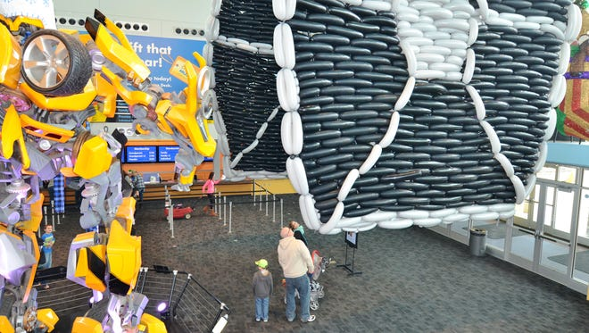 Visitors to The Children's Museum seem small in comparison to the 17-foot-tall Bumblebee Transformer statue at left and the TIE fighter balloon sculpture, at right, on Saturday, Dec. 5, 2015. The balloon sculpture, created by Indianapolis artist Brian Getz, will be on display for a week or two.