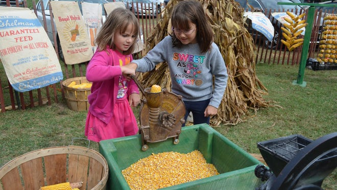 Abby Cohen, 6, and Emma Cohen, 9, both of Stow Creek, use a hand-crank corn sheller during last year's Greenwich Artisans' Faire & Marketplace.