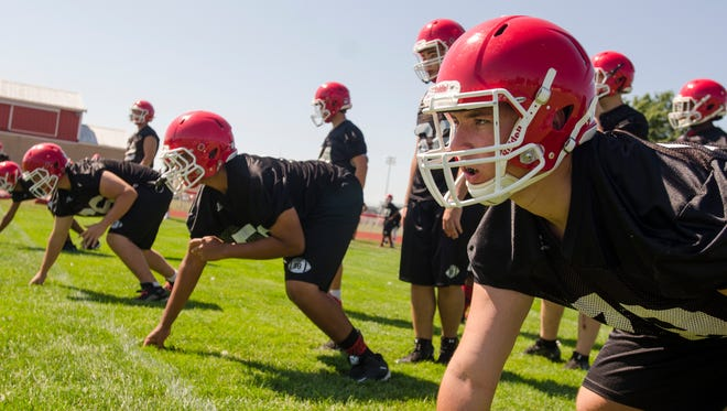 A player readies for a lineman drill during varsity football practice Monday, Aug 8, at the Port Huron High School.