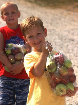 Joshua Hamrick (foreground) beams as he carries a bag of apples he picked during a visit to Anderson Orchard in Mooresville. Christopher Griffin carries his own bag in the background.