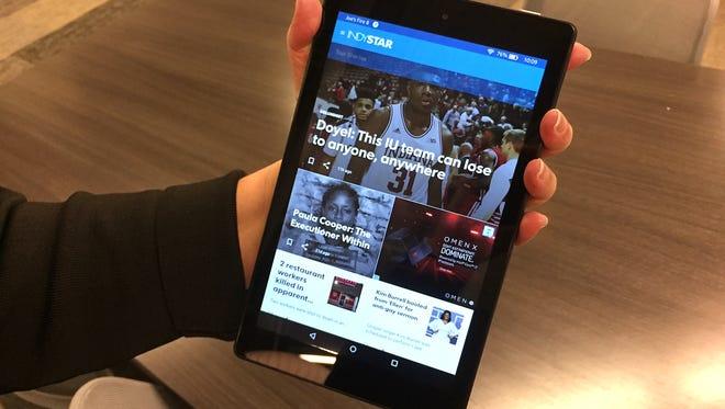 IndyStar hand model Dawn Mitchell holds an Amazon Fire HD 8 running the IndyStar app.
