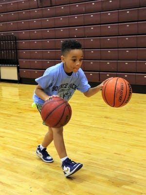 A young participant concentrates on learning the agility of bouncing two basketballs simultaneously.