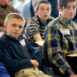 Henry Sanders, left, of St. Joseph School in Salem, listens during the Oregon State Geographic Bee at the Western Oregon University on Friday, March 27, 2015, in Monmouth, Oregon.