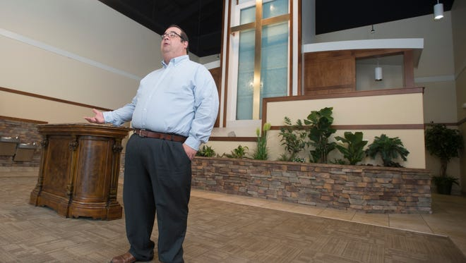 Jeff Hunt, assistant pastor of First Apostolic Church, gives a tour of the church in Milton on Thursday. The church is celebrating its 100th anniversary.