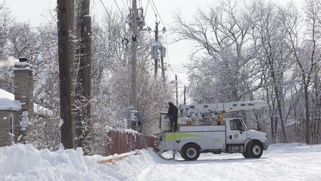 And Indianapolis Power & Light Co. worker is shown servicing a power line on Indianapolis' east side.