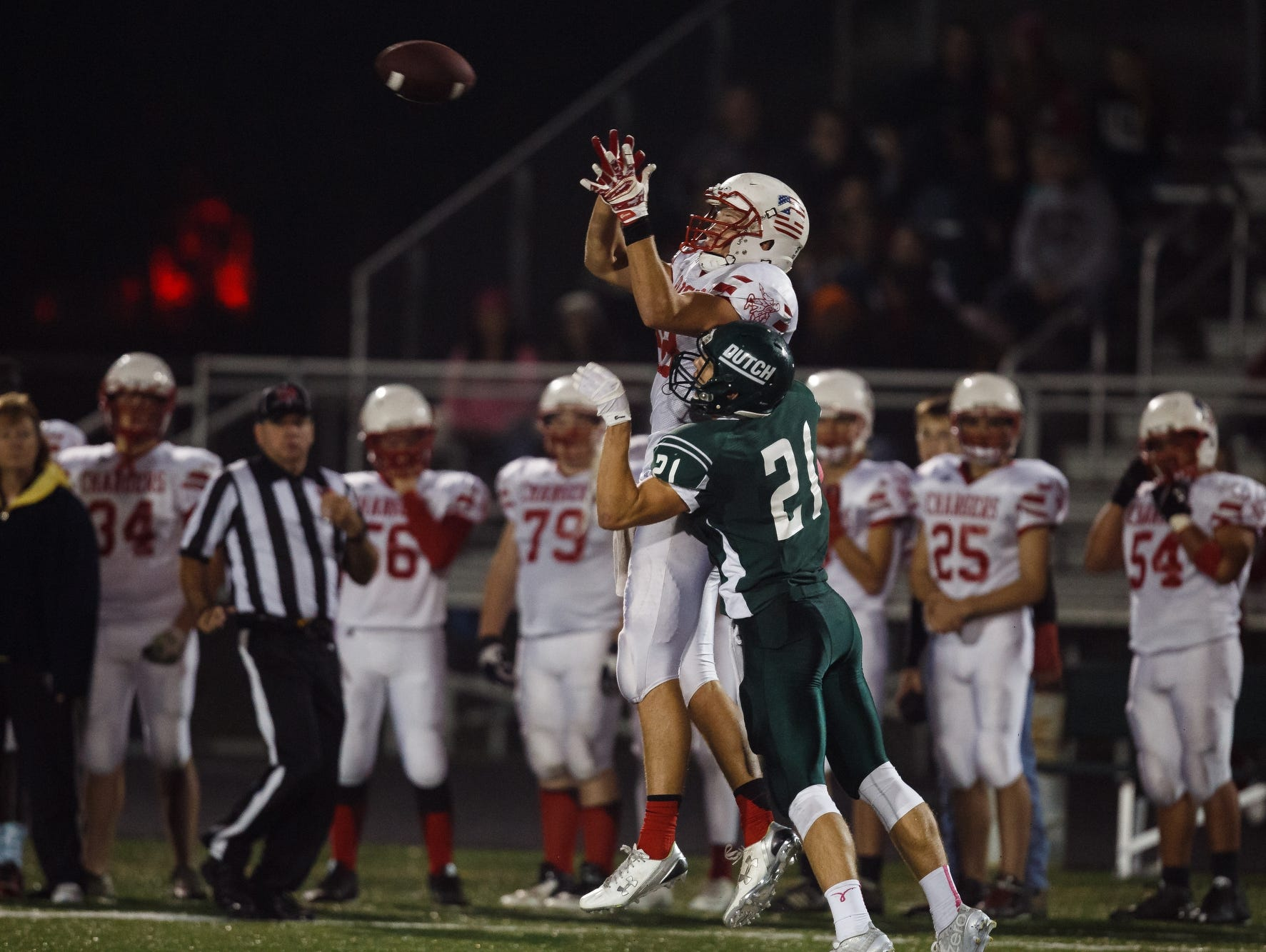 Chariton's T.J. Hockenson pulls in a pass over Pella's Will Warner during their game in Pella Friday, October 23, 2015.