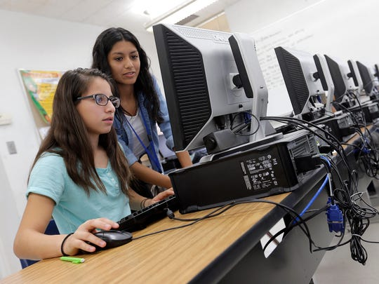 Monica Gutierrez, left, and Antoinette Hidalgo work on a project in their marketing class at Eastwood High School in this undated file photo. Tech giant Microsoft announced a partnership program for four El Paso schools that would place experienced volunteers in computer science classrooms.