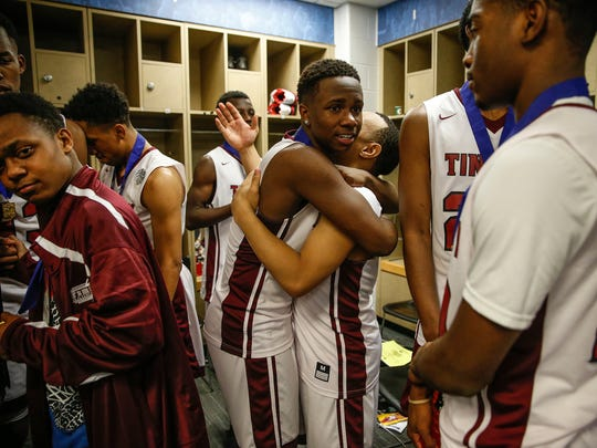 Tindley Tigers' Sincere McMahon (4) hugs teammate Tindley Tigers' Joe Johnson (0) after their IHSAA Class A state championship game 51-49 win over the Lafayette Central Catholic Knights at Bankers Life Fieldhouse in Indianapolis on Saturday, March 25, 2017.