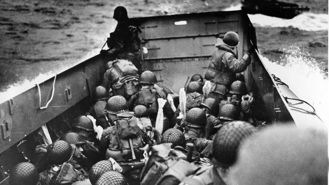 In this file photo, Allied troops crouch behind the bulwarks of a landing craft as it nears Omaha Beach during a landing in Normandy, France. The D-Day invasion broke through Adolf Hitler's western defenses and led to the liberation of France from Nazi occupation just as the Soviet Army was making advances in the east, turning the tide of the war in the Allies' favor. Allied troops landed on the Normandy coast of France in tremendous strength by cloudy daylight and stormed several miles inland with tanks and infantry in the grand assault that Gen. Dwight D. Eisenhower called a crusade in which 'we will accept nothing less than full victory.'