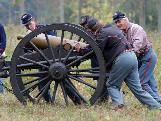 Union soldier re-enactors push a cannon on Sept. 26,