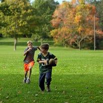 Adam Hoffman, 9, left, and Elliot Denson, 7,  both of Sheboygan, get some football in at Vollrath Park near some fall color Tuesday October 6, 2015 in Sheboygan.