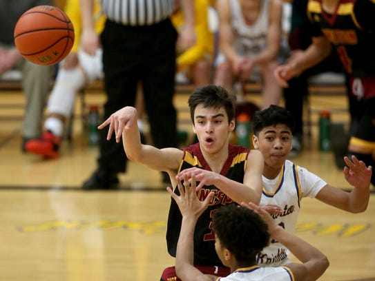 Kingston's Popeh Chiquiti makes a pass while under the pressure of Bremerton's Keith Jackmon and Kimo Retome during Friday's game.