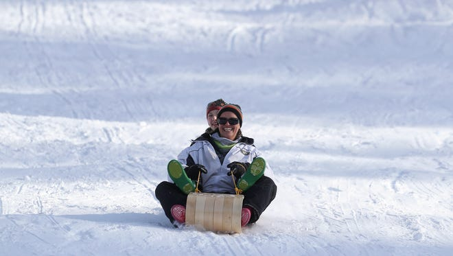 Geannine Klein, front, rides a sled with her daughter Sierra at Snowman's Hill in Mt. Shasta.