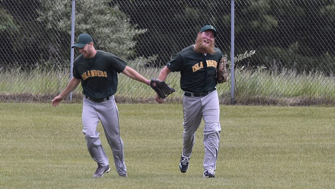 Josh Mann, left, congratulates Washington Island teammate Con McDonald for his leaping catch of a ball hit deep into right field by Institute on June 11.