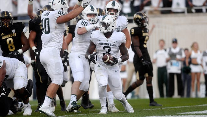 Michigan State's LJ Scott, center, celebrates his touchdown with teammates during the fourth quarter on Saturday, Sept. 9, 2017, at Spartan Stadium in East Lansing.