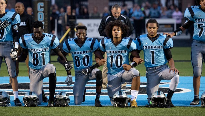 From left, Lansing Catholic's Kabbash Richards, Roje Williams, Michael Lynn III and Matthew Abdullah, kneel during the national anthem before the start of the Cougars' game against Ionia on Friday, Oct. 6, 2017, at Cougar Stadium in Lansing. The four players did not start in the game.
