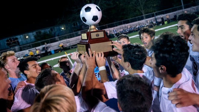 The Okemos boys soccer team celebrates with their trophy during the second half on Tuesday, Oct. 6, 2017, at Grand Ledge High School. Okemos won the Capitol Area Activities Conference Gold Cup Division championship 3-1.
