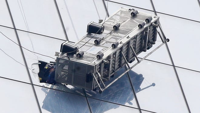 A firefighter reaches through a cut-out window into a dangling work basket to rescue two workers from the 60th floor of 1 World Trade in New York, Wednesday, Nov. 12, 2014. The two window washers were trapped for more than an hour.  The dramatic rescue occurred on the south side of the 1,776-foot, 104-story building, where the open-topped platform hung at about a 45-degree angle and swayed slightly in the wind.