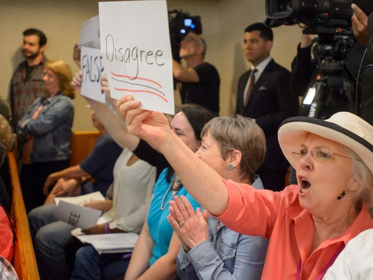 Residents hold signs to stress their dissaproval of