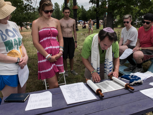 Rabbi Alon Ferency reads from a small Torah during a Shabbat service Saturday at Bonnaroo Music and Arts Festival.