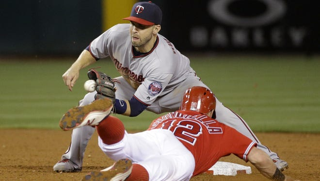 The Los Angeles Angels' Johnny Giavotella, bottom, steals second base against Minnesota Twins second baseman Brian Dozier during the sixth inning Tuesday in Anaheim, Calif.