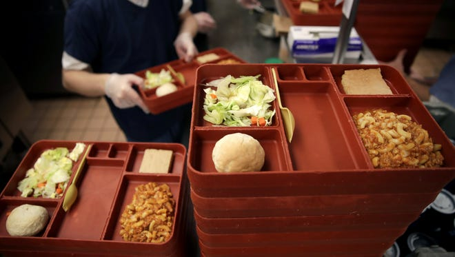 An inmate at the Outagamie County Jail stacks food trays before they are delivered for lunch last week.  Lunch consisted of a roll, cake, salad and goulash. Danny Damiani/USA TODAY NETWORK-Wisconsin
