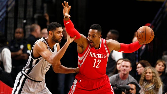 Houston Rockets center Dwight Howard (12) is defended by San Antonio Spurs power forward Tim Duncan (L) during the first half at AT&T Center.