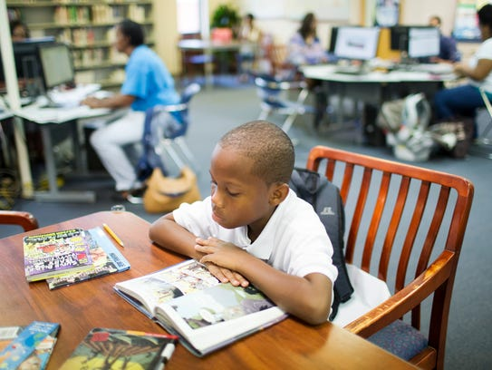 Grant Eady, 9, reads in the library at Montgomery Catholic