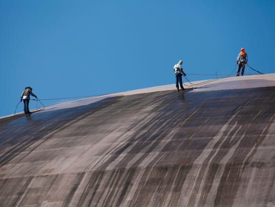 Workers pressure wash the roof of the Cajundome as