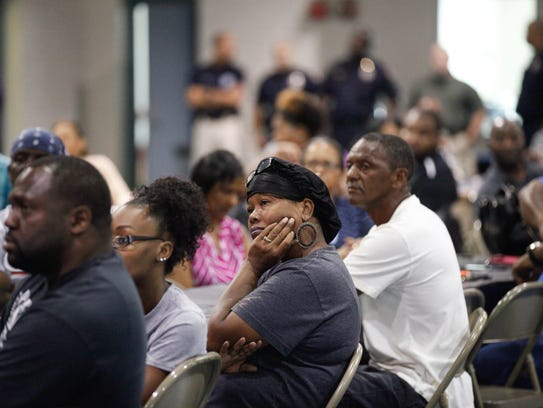 Residents listen to proceedings during a meeting to