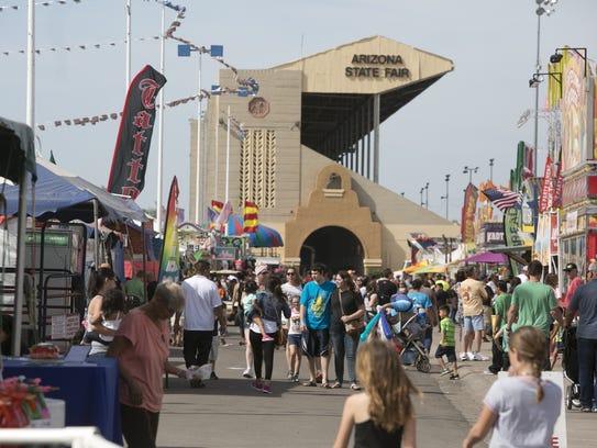Fair goers walk the streets of the Arizona State Fair