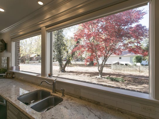 A picture window overlooks the tree-shaded backyard