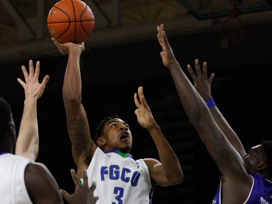 FGCU's Julian DeBose scores over Corpus Christi's Rashawn Thomas during first-half play at the 2015CTI.com tournament Wednesday.