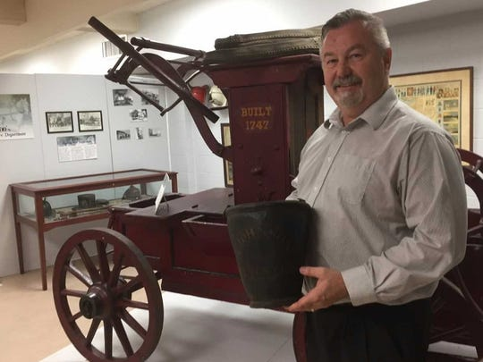 Jack O'Byrne, executive director of the Camden County Historical Society, holds a fire bucket in the organization's Camden museum.
