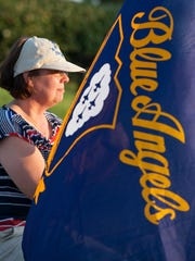 Judy Seward, of Pensacola, holds a Blue Angels flag during the Candle light vigil for fallen Blue Angels - Marine Capt. Jeff Kuss in Veterans Memorial Park in Pensacola, FL on Thursday, June 9, 2016.