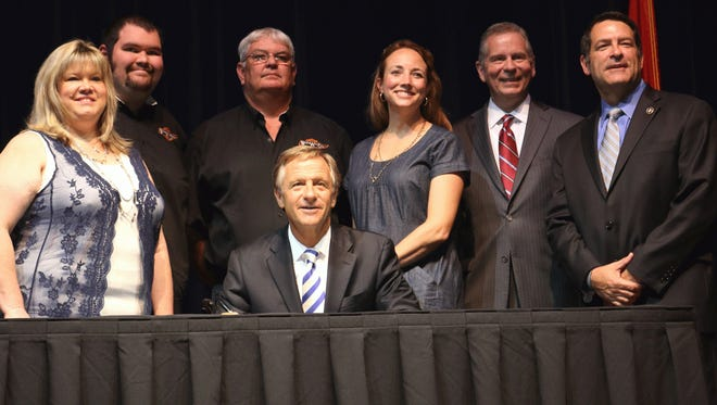 """Margaret Davis, left, and her family at the signing into law this week of the new """"Care Alert"""" by Governor Bill Haslam, seated, and lawmakers Senator Mark Green, right, and Representative Joe Pitts, second from right."""
