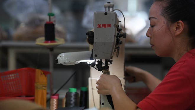 File photo taken in Sept. 2016 shows a worker at the Huajian shoe factory in Dongguan, China, where about 100,000 pairs of Ivanka Trump-branded shoes and footwear of other companies  have been made over the years.