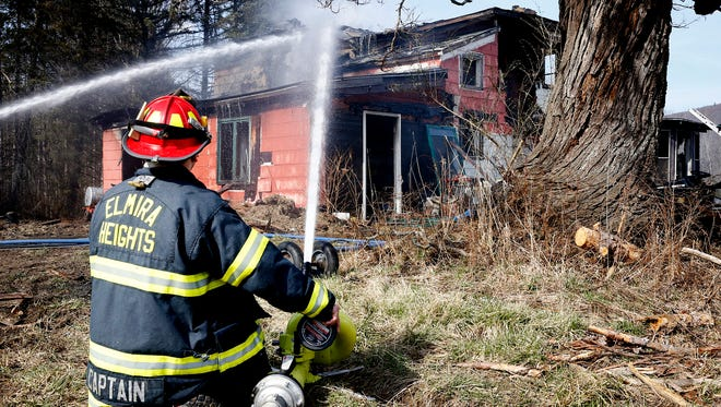 An Elmira Heights fire captain blasts water onto the rear of a Bentley Road home in Wellsburg Thursday afternoon.